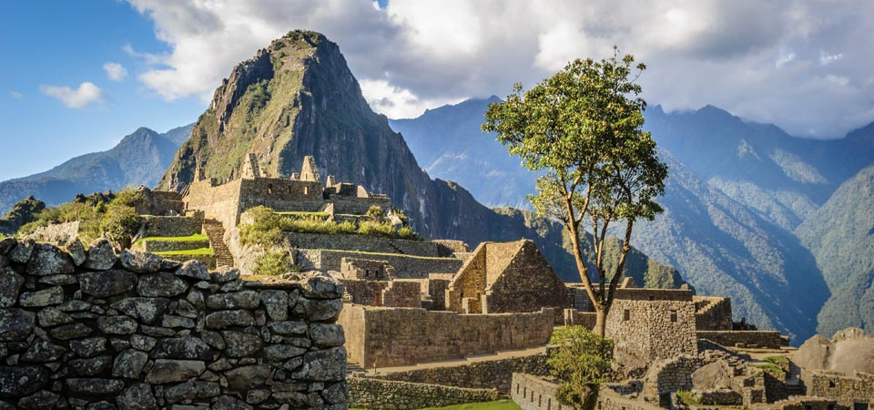 Stone buildings overlooked by a mountain peak at Machu Picchu, the famous Lost City of the Incas.