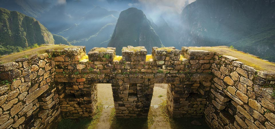 Two stone windows and the sun shining over a mountain peak off in the distance at Machu Picchu.