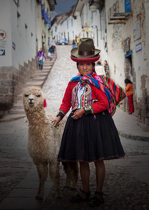 A woman wearing traditional Quechua clothing stands next to an alpaca with a narrow street behind