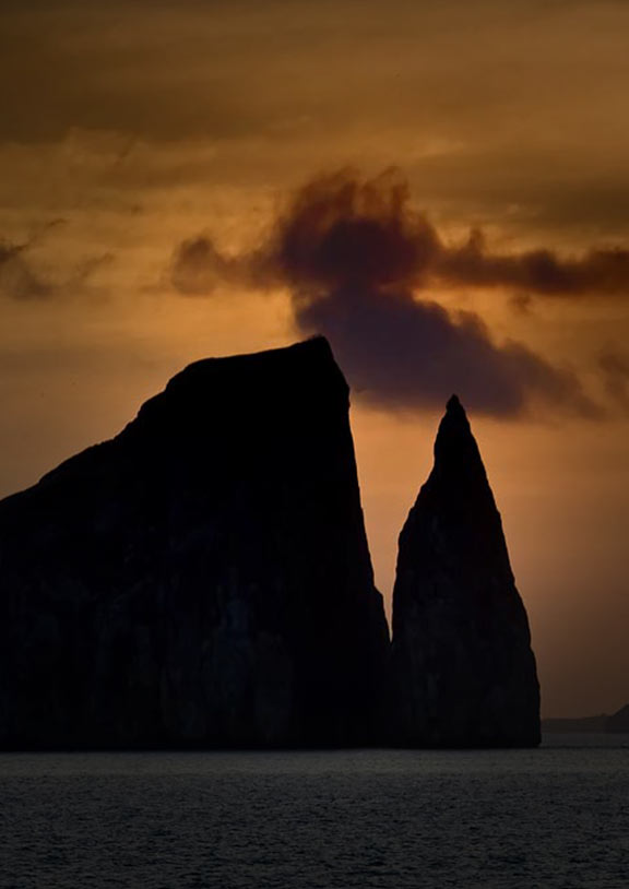 A sunset silhouettes Kicker Rock, a jagged rock formation jutting out of the ocean in the Galapagos.