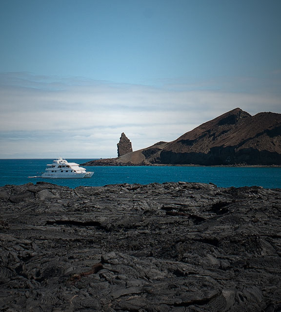 A yacht sails around dried lava flows and volcanic rock formations in the Galapagos Islands.