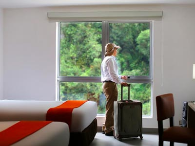 A visitor with a suitcase looking out at the window in a room at Casa Andina Standard Machu Picchu.