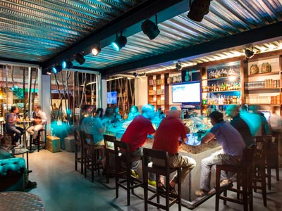 Visitors enjoying drinks at the sleek modern bar of El Mapi, a 4-star hotel near Machu Picchu.