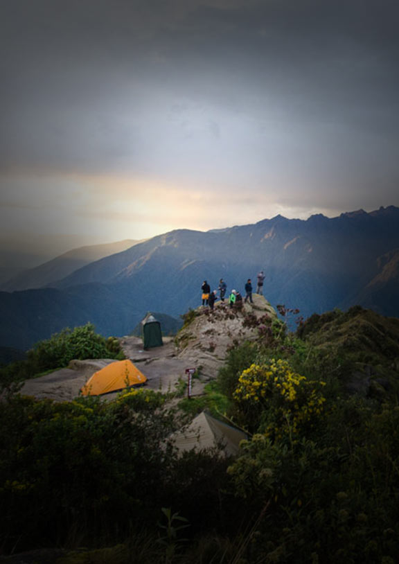 Inca Trail campsite with tents set up and trekkers on a ledge peaking over mountainous terrain