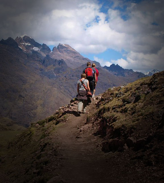 Hikers walking in front of the Andes Mountains on the Lares Trek