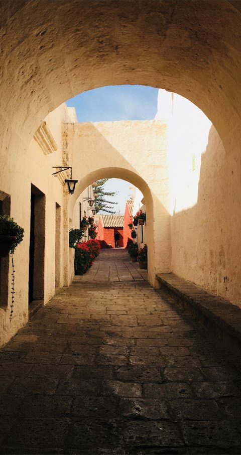A stone path passing under a couple of archways at the Santa Catalina Monastery in Arequipa.