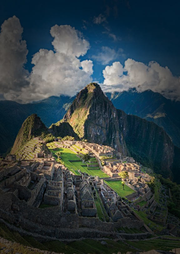 Overlooking the Incan citadel Machu Picchu surrounded by mountains with clouds in the sky
