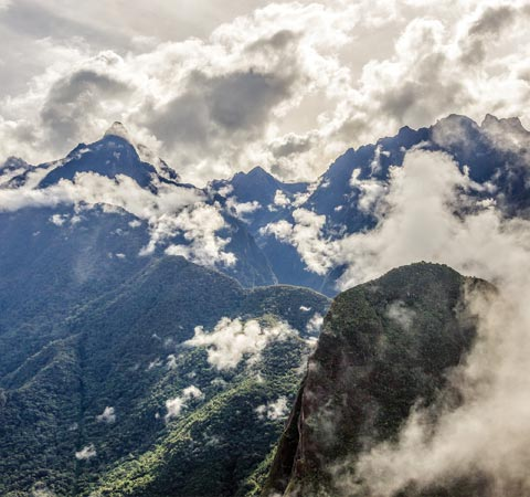 Clouds rolling over the vegetation-covered peaks of the Andes Mountains near Machu Picchu.
