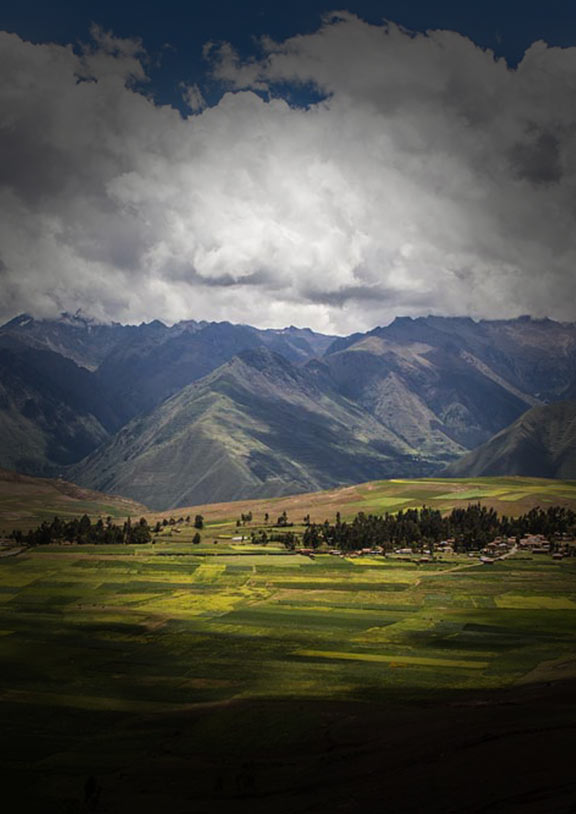 Vast green landscape in the Sacred Valley with Andes Mountains behind and clouds above