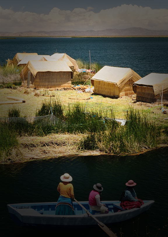 A row boat approaches the floating Uros Islands made of totora reed in Lake Titicaca