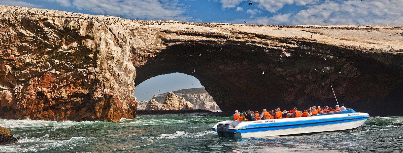 Desert cliffs overlooking a narrow strip of beach on the Pacific Ocean in Paracas.