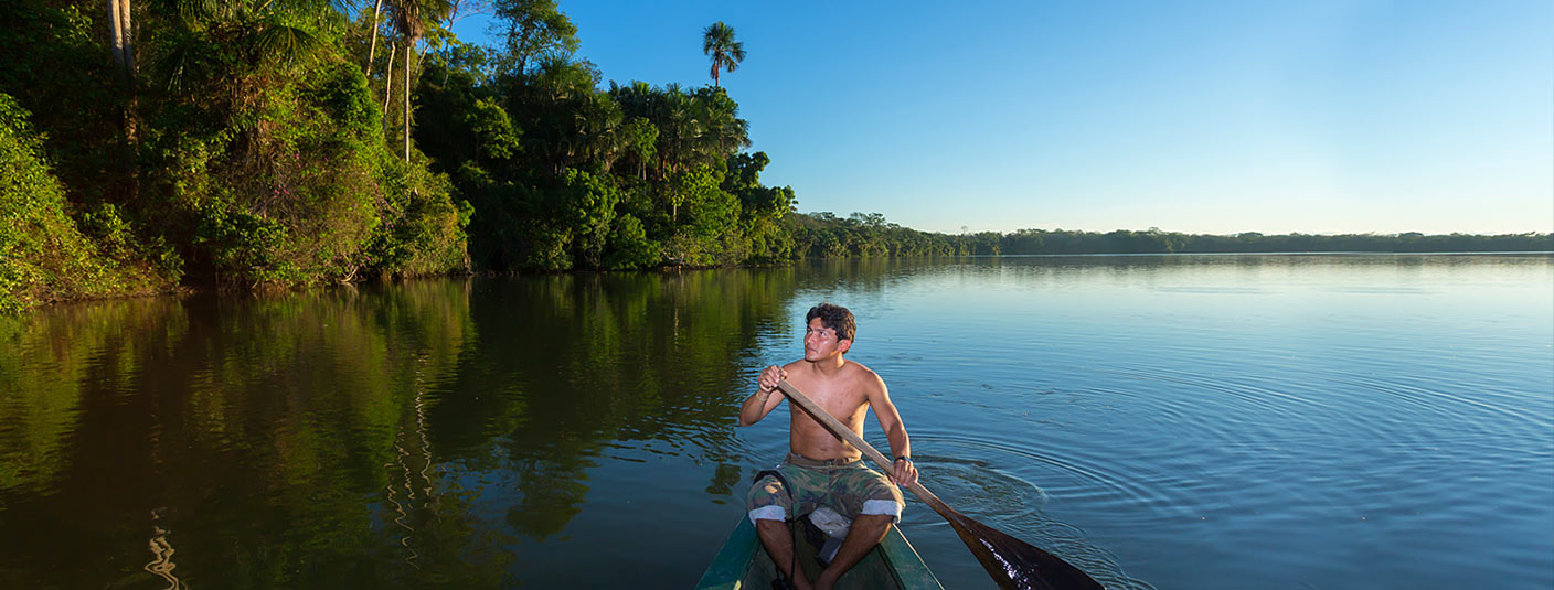 A shirtless man paddling a canoe down a river in the Peruvian Amazon Rainforest.