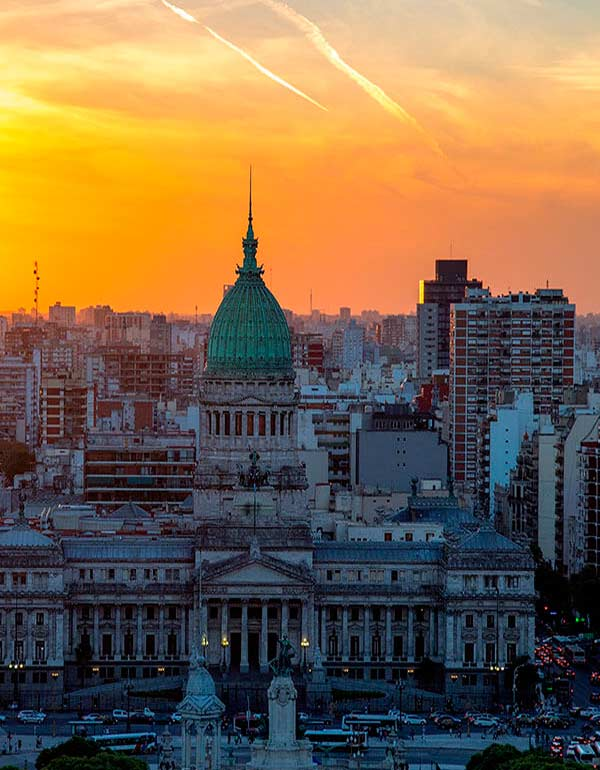 A sunset Buenos Aires city skyline with the Palace of the Argentine National Congress in the front.