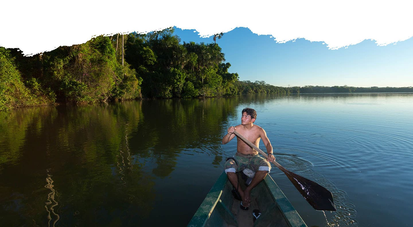 Man paddling on a boat in the Amazon
