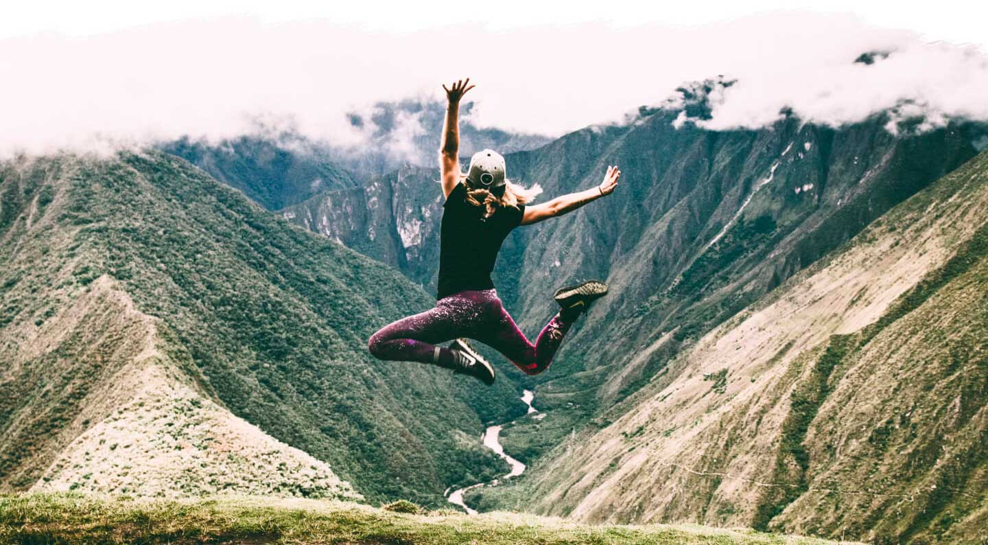 Girl jumping in front of the Urubamba River at Machu Picchu