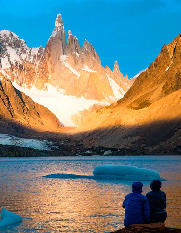 Two people watch the sunset on the jagged Cerro Torre mountain as icebergs float in Laguna Torre.