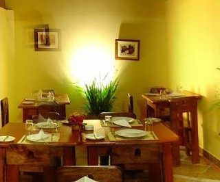 A few tables set for dinner decorated by small paintings and a plant | Inti Orquideas Hotel | Peru for Less