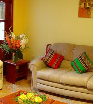 Room with couch and small tables decorated with flowers | Inti Orquideas Hotel | Peru for Less