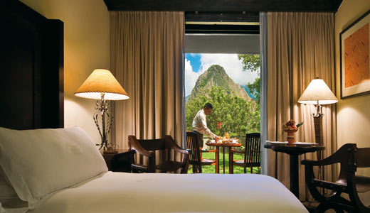 Single room with view of patio where hotel staff sets a table with the mountains of Macchu Picchu in the background | Sanctuary Lodge | Peru for Less