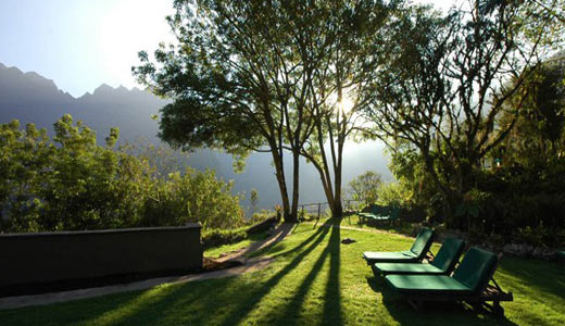 Common outdoor area with small trees and bushes, lounge chairs and a clear view of the surrounding hills | Sanctuary Lodge | Peru for Less