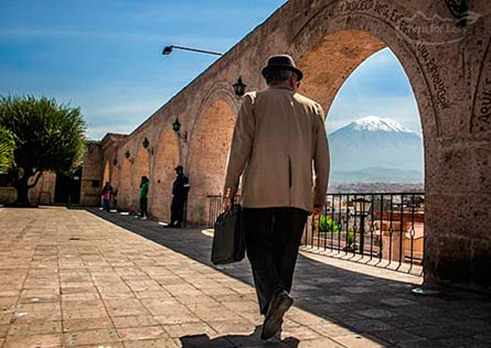 Man carrying a briefcase walking in Arequipa with view of Misti in the background