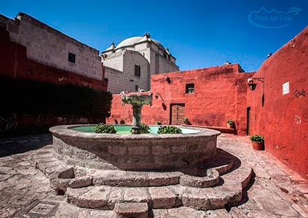 Courtyard with deep red walls surrounding a fountain at the Santa Catalina Monestary