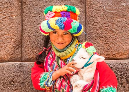 A smiling young girl in bright local Cusco dress holding a baby white lamb in her arms