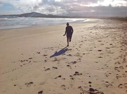 Girl running on beach on Isabela Island.