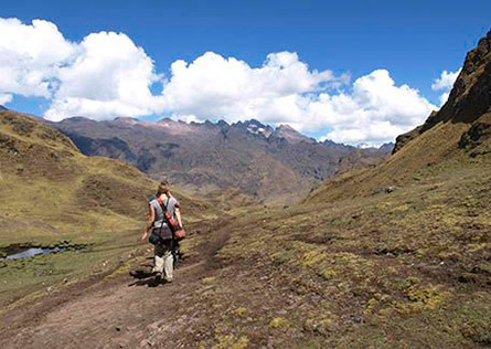 Two hikers walking along the Lares Trail towards Andean peaks