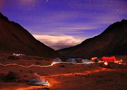 Silhouette of high mountain peaks surrounding the lights of a camping site