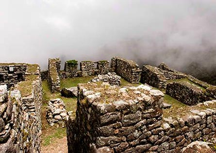 Ruins along the Inca Trail with thick white clouds behind