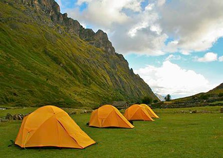 Four yellow tents in a green valley surrounded by mountains along the Inca Trail