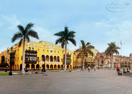 View of a large colonial building around Lima's Plaza de Armas lined by palm trees