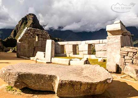 Three window structures in a stone ruins of Machu Picchu with Machu Picchu behind