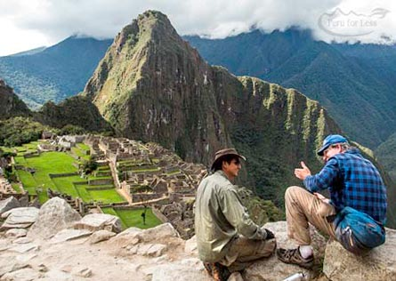 Guide talking to traveler with Machu Picchu behind them
