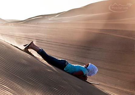 Traveler riding a sandboard on their stomach in dunes of Huacachina