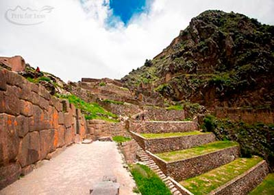 Dirt path leading to the green terraces of the Ollantaytambo ruins
