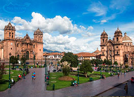 View of people walking through the Plaza de Armas in Cusco on a sunny day.