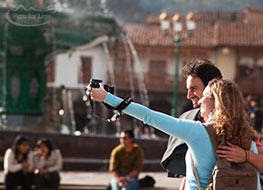A couple taking their photo in the plaza of Cusco