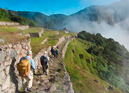 Travelers walking along the trail from the Sun Gate to the Machu Picchu Citadel