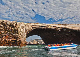 A boat filled with passengers touring the rocky Ballestas Islands.