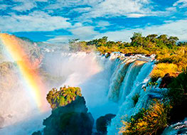 Raging water falling over the Iguazu with a rainbow