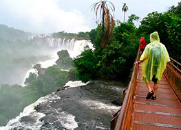 View at the top of Iguazu Falls with a guy in a yellow rain poncho