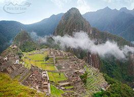 Machu Picchu from afar with a thin cloud lingering over ruins