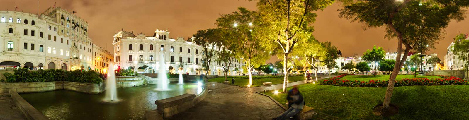 White colonial buildings surround a plaza in historic Lima by night