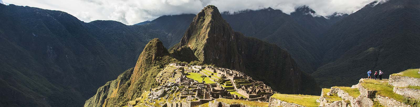 View over Machu Picchu Citadel atop mountain with river far below in the valley