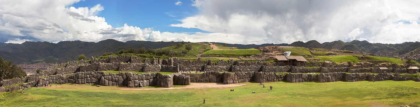 Humans appear tiny next to the giant stone ruins of Sacsayhuaman
