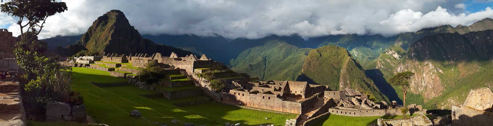 Panoramic view of Machu Picchu ruins with cloud forest in the background