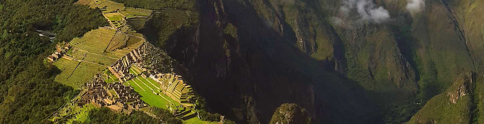 View of Machu Picchu ruins, surrounded by the clouf forest, from the top of Huayna Picchu Mountain