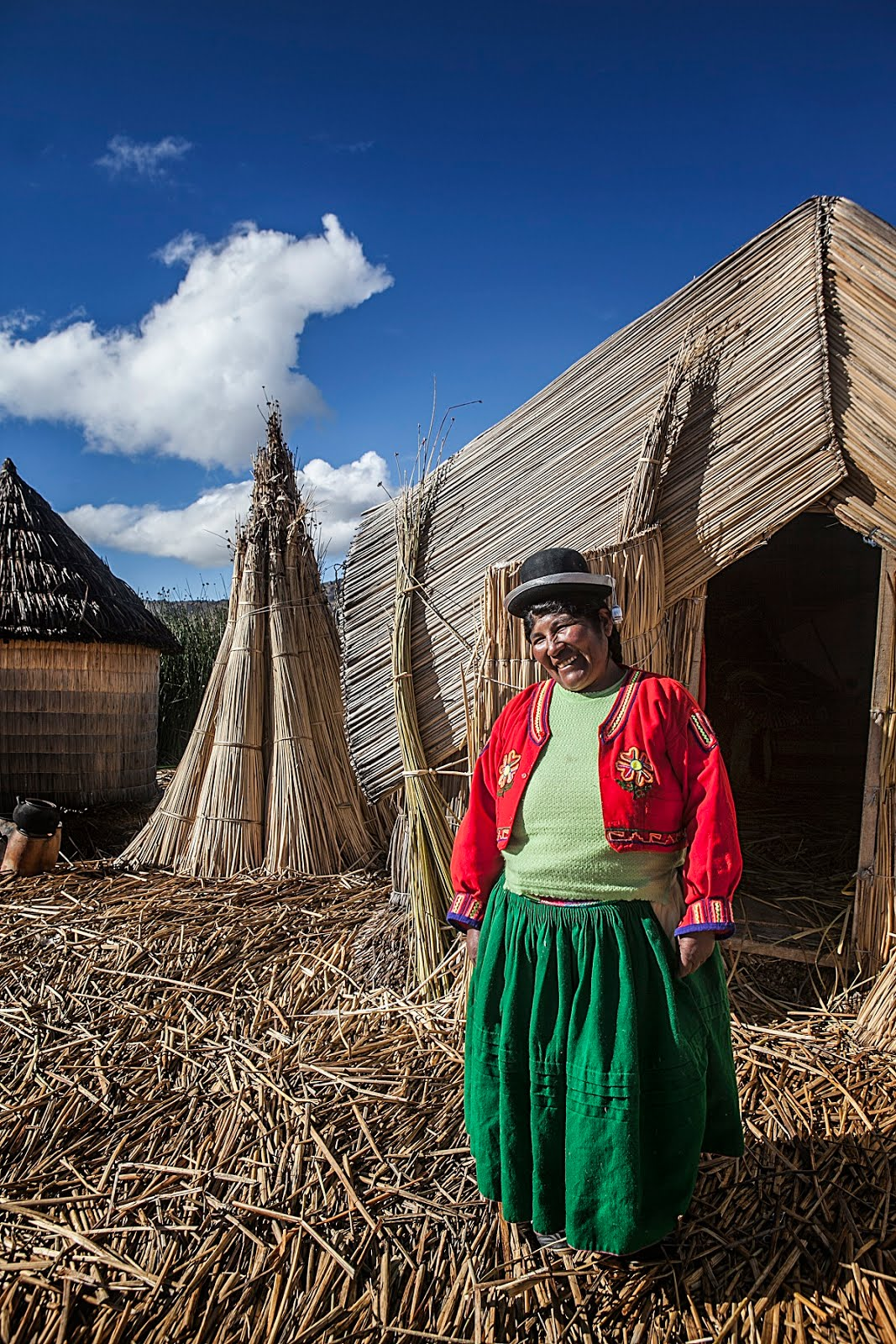 Uros woman in front of her island cabin, Lake Titicaca, Peru